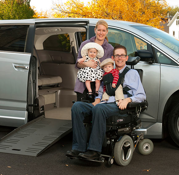 Family with father in wheelchair next to their van.